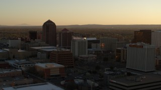 DX0002_122_040 - 5.7K stock footage aerial video of high-rise office buildings at sunset during descent and flying away, Downtown Albuquerque, New Mexico