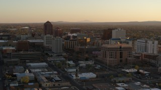 DX0002_122_042 - 5.7K stock footage aerial video of a reverse view of high-rise office buildings at sunset and ascend, Downtown Albuquerque, New Mexico