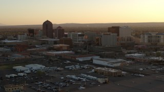 DX0002_122_044 - 5.7K stock footage aerial video pass and then approach high-rise office buildings at sunset, Downtown Albuquerque, New Mexico