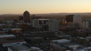 DX0002_122_045 - 5.7K stock footage aerial video approach and then flyby office high-rises at sunset, Downtown Albuquerque, New Mexico