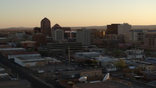 DX0002_122_046 - 5.7K stock footage aerial video fly away from office high-rises at sunset during descent, Downtown Albuquerque, New Mexico