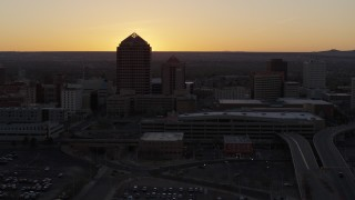 DX0002_122_049 - 5.7K stock footage aerial video ascend to reveal sunset behind office tower and shorter hotel tower, Downtown Albuquerque, New Mexico