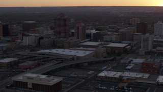 DX0002_122_050 - 5.7K stock footage aerial video slow orbit of an office tower and shorter hotel tower behind convention center at sunset, Downtown Albuquerque, New Mexico