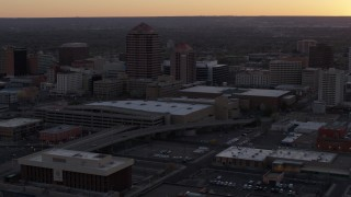DX0002_122_051 - 5.7K stock footage aerial video orbit office tower and shorter hotel tower behind convention center at sunset, Downtown Albuquerque, New Mexico