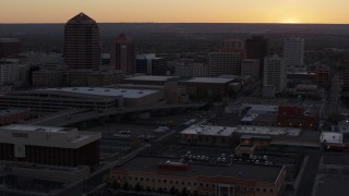 DX0002_122_054 - 5.7K stock footage aerial video flyby office high-rises and convention center near office tower and shorter hotel tower at sunset, Downtown Albuquerque, New Mexico