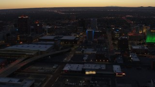 DX0002_123_024 - 5.7K stock footage aerial video flying away from hotel and office buildings at twilight, Downtown Albuquerque, New Mexico