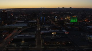 DX0002_123_027 - 5.7K stock footage aerial video wide orbit of hotel with blue lighting near office buildings at twilight, Downtown Albuquerque, New Mexico