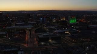 DX0002_123_028 - 5.7K stock footage aerial video DoubleTree hotel with blue lighting near office buildings at twilight, Downtown Albuquerque, New Mexico