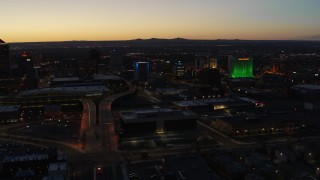DX0002_123_029 - 5.7K stock footage aerial video of the DoubleTree hotel with blue lighting near office buildings at twilight, Downtown Albuquerque, New Mexico