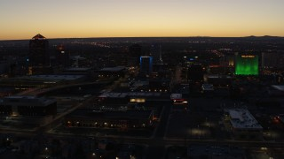 DX0002_123_030 - 5.7K stock footage aerial video of passing DoubleTree hotel with blue lighting near office buildings at twilight, Downtown Albuquerque, New Mexico