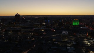 DX0002_123_031 - 5.7K stock footage aerial video flyby and approach DoubleTree hotel with blue lighting near office buildings at twilight, Downtown Albuquerque, New Mexico