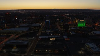 DX0002_123_032 - 5.7K stock footage aerial video ascend and orbit DoubleTree hotel with blue lighting near office buildings at twilight, Downtown Albuquerque, New Mexico