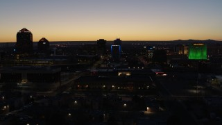 DX0002_123_034 - 5.7K stock footage aerial video descend past hotel with blue lighting near office towers at twilight, Downtown Albuquerque, New Mexico