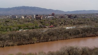 DX0002_124_002 - 5.7K stock footage aerial video of high-rise office buildings seen while ascending by the Rio Grande, Downtown Albuquerque, New Mexico