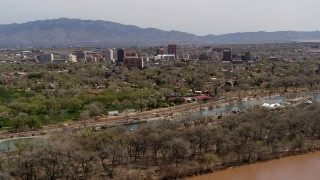 DX0002_124_005 - 5.7K stock footage aerial video approach high-rise office buildings while ascending over the Rio Grande and park, Downtown Albuquerque, New Mexico