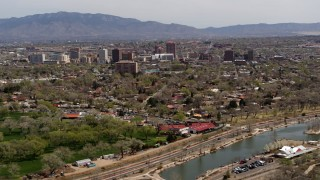 DX0002_124_006 - 5.7K stock footage aerial video flying by high-rise office buildings seen from Tingley Beach, Downtown Albuquerque, New Mexico