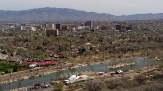 DX0002_124_007 - 5.7K stock footage aerial video flying by high-rise office buildings, descend by park, Downtown Albuquerque, New Mexico