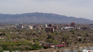 DX0002_124_018 - 5.7K stock footage aerial video descend with wide view of high-rise office buildings, distant mountains, Downtown Albuquerque, New Mexico