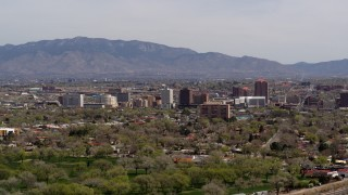 DX0002_124_019 - 5.7K stock footage aerial video descend with wide view of high-rise office buildings, distant mountains, Downtown Albuquerque, New Mexico