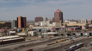 DX0002_124_020 - 5.7K stock footage aerial video of an office high-rise seen from train tracks, Downtown Albuquerque, New Mexico