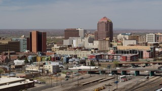 DX0002_124_021 - 5.7K stock footage aerial video of an office high-rise seen while ascending near train tracks, Downtown Albuquerque, New Mexico