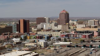 DX0002_124_022 - 5.7K stock footage aerial video of an office high-rise towering over city buildings, Downtown Albuquerque, New Mexico