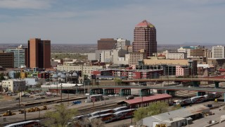 DX0002_124_023 - 5.7K stock footage aerial video office high-rise towering over city buildings, seen from railroad tracks, Downtown Albuquerque, New Mexico