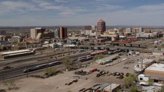 DX0002_124_029 - 5.7K stock footage aerial video passing railroad tracks with view of Albuquerque Plaza and surrounding buildings, Downtown Albuquerque, New Mexico