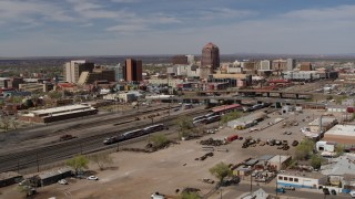 DX0002_124_033 - 5.7K stock footage aerial video approach train tracks with office buildings in the background, Downtown Albuquerque, New Mexico