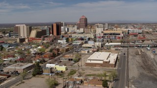 DX0002_124_036 - 5.7K stock footage aerial video reverse view of office buildings, and flyby railroad tracks, Downtown Albuquerque, New Mexico