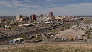 DX0002_124_037 - 5.7K stock footage aerial video descend and fly away from train tracks with office buildings in the distance, Downtown Albuquerque, New Mexico