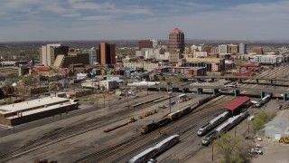 DX0002_124_038 - 5.7K stock footage aerial video approach train tracks and office buildings in the distance, Downtown Albuquerque, New Mexico