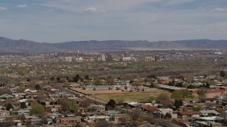DX0002_126_001 - 5.7K stock footage aerial video flying by suburban homes with a view of Downtown Albuquerque in the distance, New Mexico