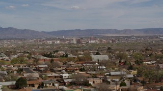 DX0002_126_002 - 5.7K stock footage aerial video passing by suburban homes with a view of Downtown Albuquerque in the background, New Mexico