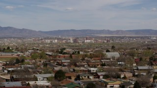DX0002_126_003 - 5.7K stock footage aerial video flyby suburban homes with a view of Downtown Albuquerque in the distance, New Mexico
