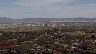 DX0002_126_004 - 5.7K stock footage aerial video ascend past suburban homes with a view of Downtown Albuquerque in the distance, New Mexico