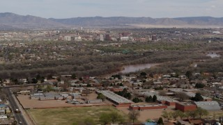 DX0002_126_008 - 5.7K stock footage aerial video ascend over suburban neighborhood with Downtown Albuquerque beyond Rio Grande, New Mexico
