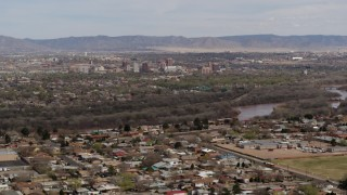 DX0002_126_009 - 5.7K stock footage aerial video of Downtown Albuquerque beyond Rio Grande, seen from suburban homes, New Mexico