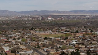 DX0002_126_010 - 5.7K stock footage aerial video fly away from Downtown Albuquerque and Rio Grande, seen from suburban homes, New Mexico