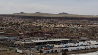 DX0002_126_015 - 5.7K stock footage aerial video of suburban neighborhood across freeway, descend near warehouse building in Albuquerque, New Mexico