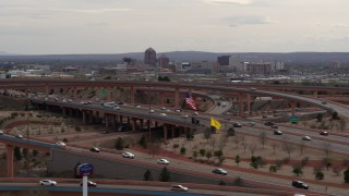 DX0002_126_019 - 5.7K stock footage aerial video ascend past freeway interchange to focus on Downtown Albuquerque, New Mexico