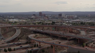DX0002_126_023 - 5.7K stock footage aerial video of Downtown Albuquerque seen while passing freeway interchange traffic, New Mexico