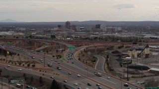 DX0002_126_028 - 5.7K stock footage aerial video of Downtown Albuquerque buildings seen while descending past freeway interchange traffic, New Mexico