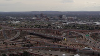 DX0002_126_029 - 5.7K stock footage aerial video of Downtown Albuquerque buildings seen while flying by freeway interchange traffic, New Mexico