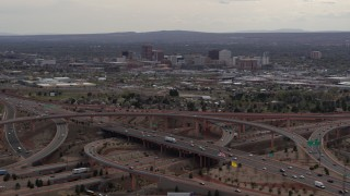 DX0002_126_030 - 5.7K stock footage aerial video of Downtown Albuquerque buildings seen while passing freeway interchange traffic, New Mexico