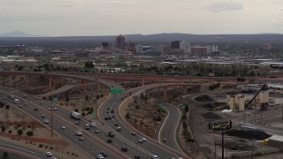 DX0002_126_031 - 5.7K stock footage aerial video of Downtown Albuquerque buildings seen while descending by freeway interchange traffic, New Mexico