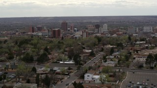 DX0002_126_043 - 5.7K stock footage aerial video wide view of city's high-rises seen while flying by homes, Downtown Albuquerque, New Mexico