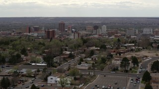 DX0002_126_044 - 5.7K stock footage aerial video wide view of city's high-rises seen while slowly passing homes, Downtown Albuquerque, New Mexico