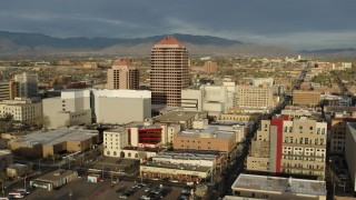 DX0002_127_030 - 5.7K stock footage aerial video wide orbit of Albuquerque Plaza towering over city buildings, Downtown Albuquerque, New Mexico