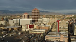 DX0002_127_031 - 5.7K stock footage aerial video wide orbit of Albuquerque Plaza high-rise towering over city buildings, Downtown Albuquerque, New Mexico